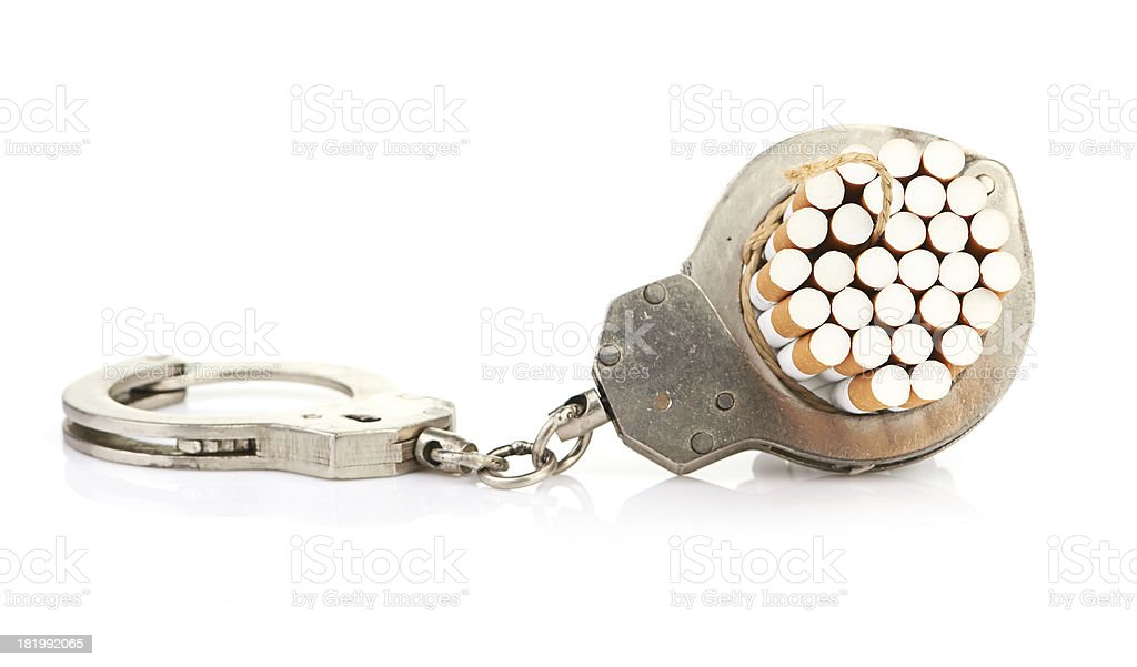 Addition concept with cigarettes and handcuffs royalty-free stock photo