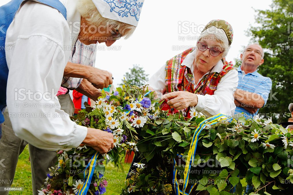 Adheres wreath of flowers at the Maypole stock photo