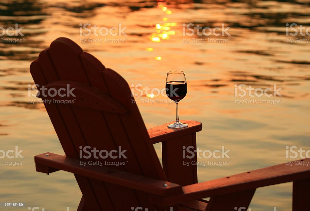 Adirondack Chair and Wine at Sunset By Lake stock photo