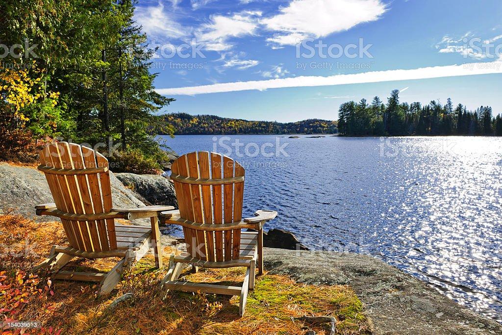 Adirondack chairs at lake shore stock photo