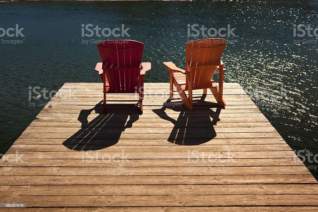 Adirondack chairs on a dock stock photo