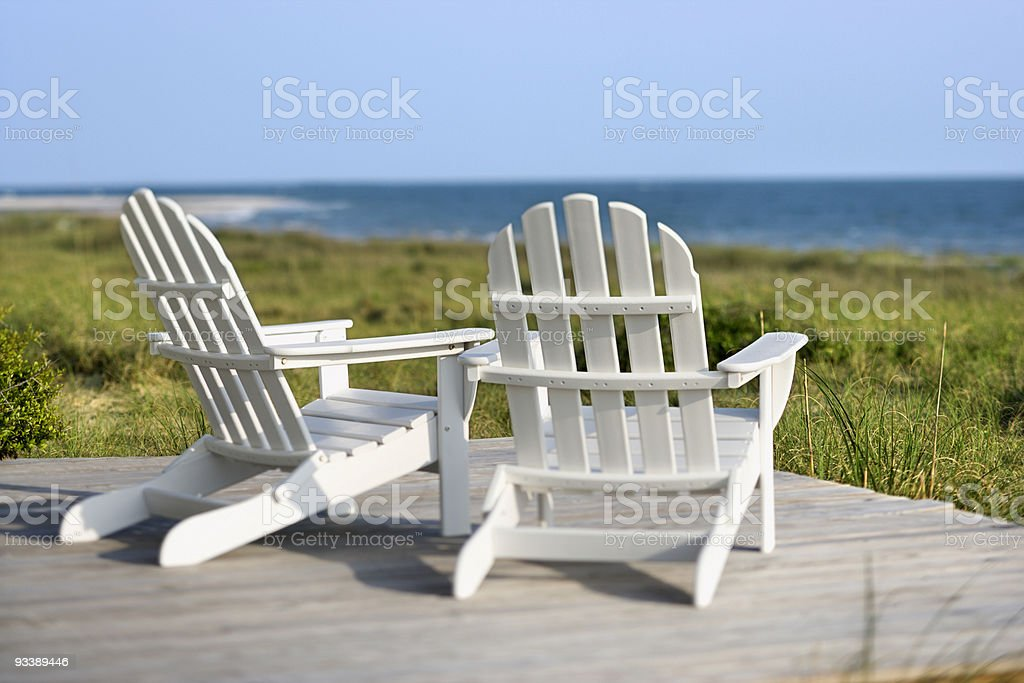adirondack chairs overlooking grassy beach and ocean stock photo