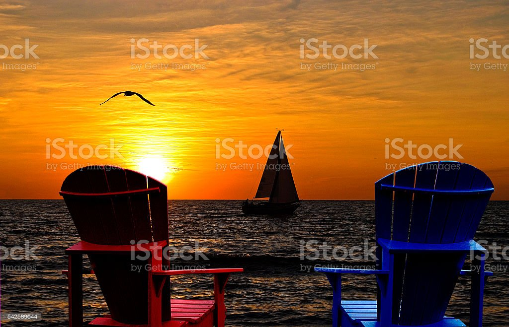 Adirondack chairs overlooking sunset on Lake Michigan stock photo