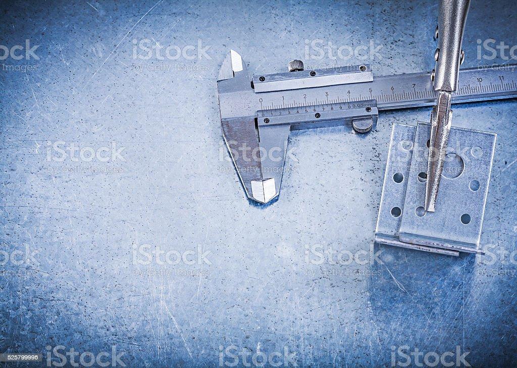Adjustable pliers wrench slide caliper angle bars on metallic ba stock photo