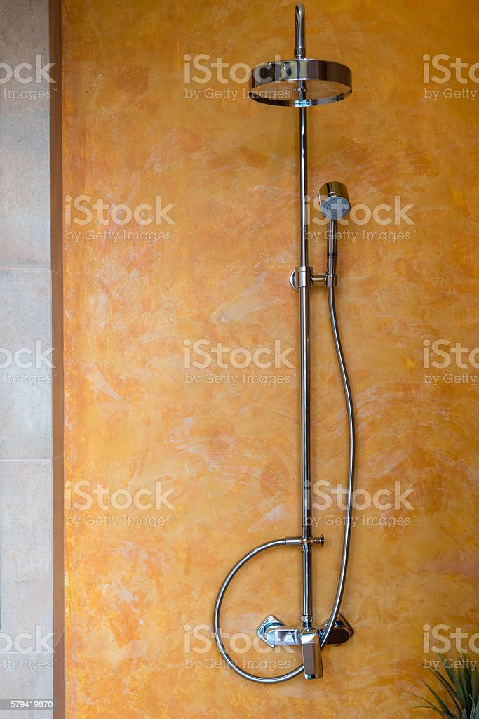 adjustable shower faucet hanging on yellow and orange bathroom wall stock photo
