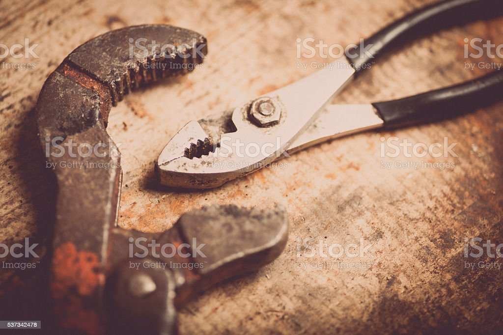 Adjustable spanner and pliers on wooden plank stock photo