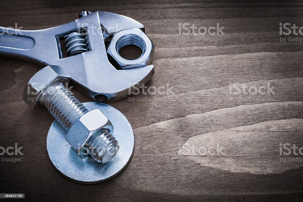 Adjustable spanner bolt washer screw-nut and screwbolt on wooden stock photo