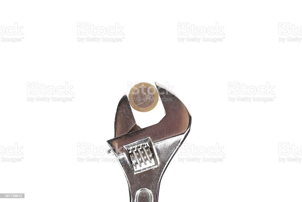Adjustable wrench holding coin royalty-free stock photo