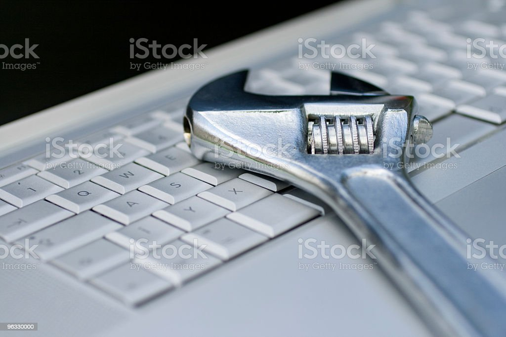 Adjustable wrench on a laptop royalty-free stock photo