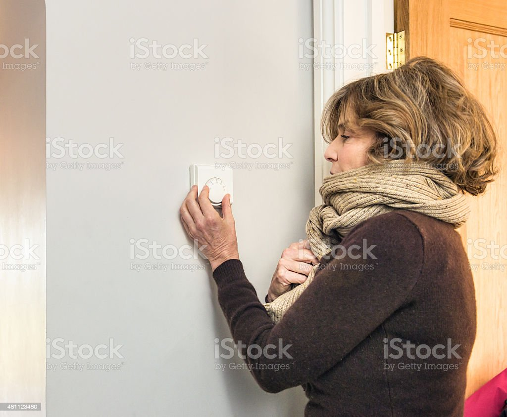 Adjusting the heating thermostat stock photo