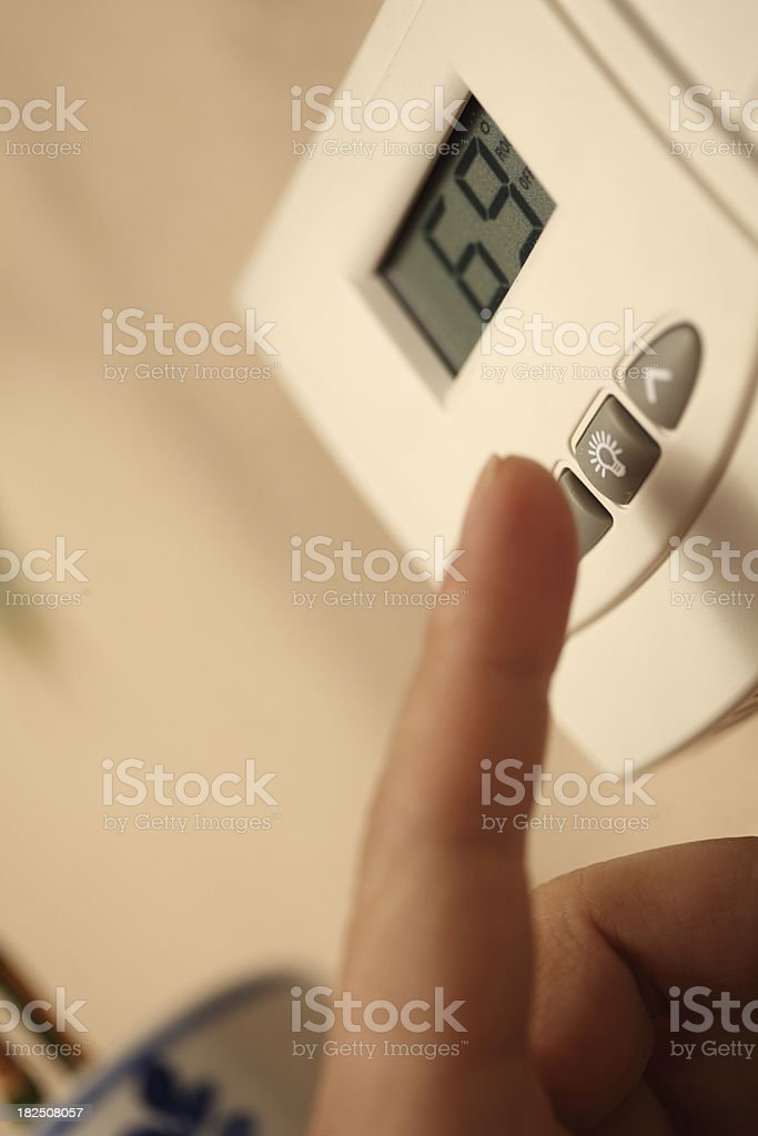 adjusting the thermostat royalty-free stock photo