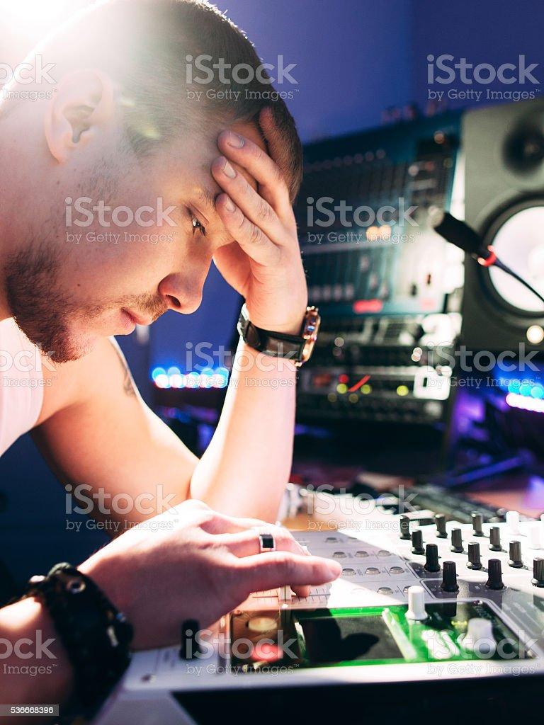 DJ adjusts music equipment before starting work stock photo