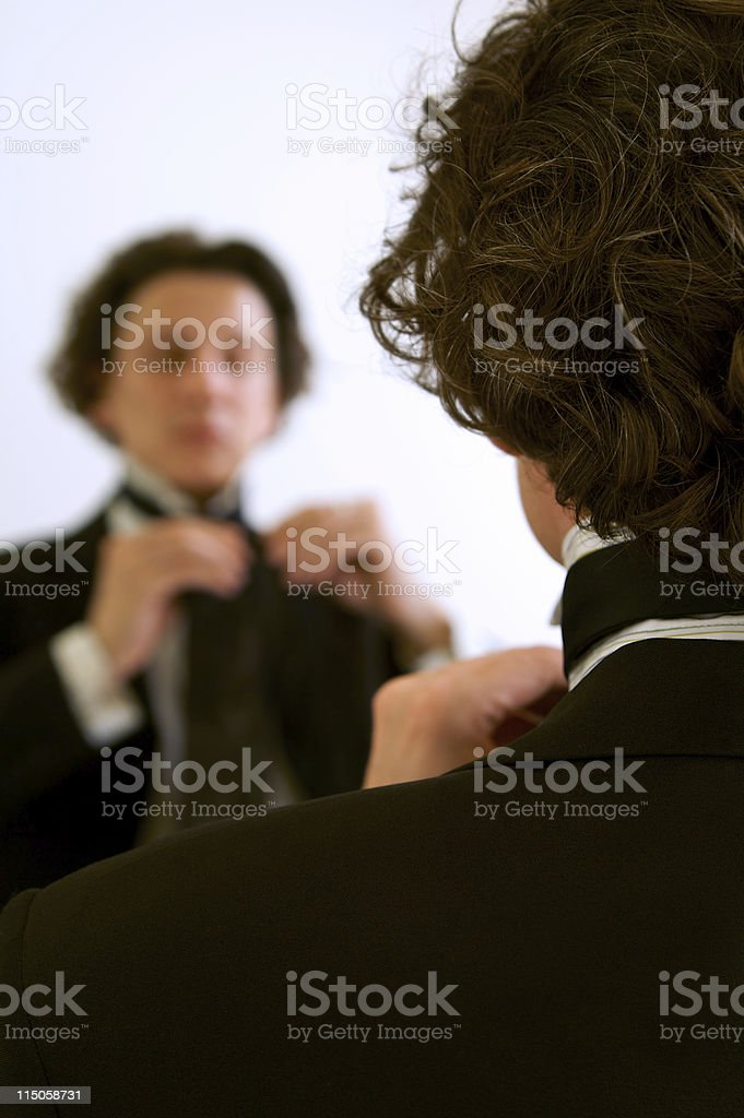 Adjuting Tie in the mirror royalty-free stock photo