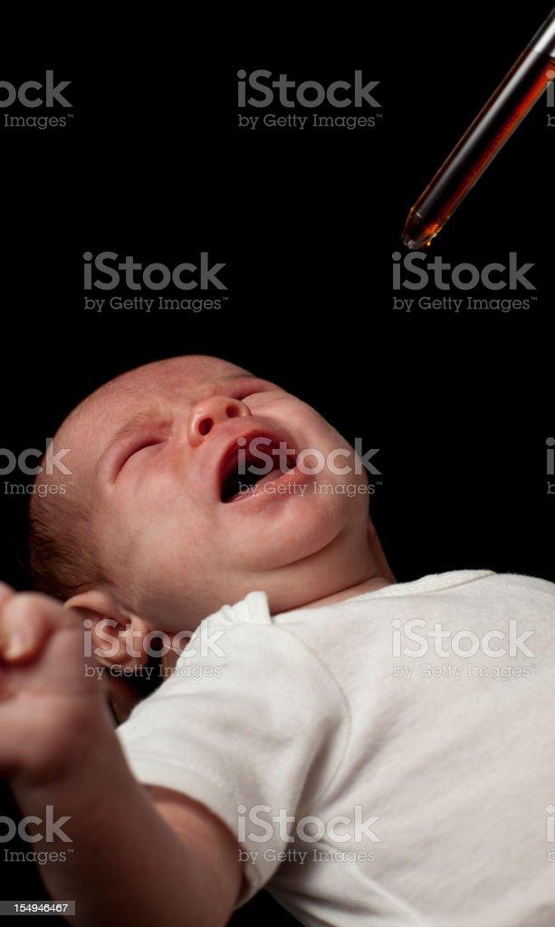 Administering Liquid Medicine to Crying Newborn Baby royalty-free stock photo