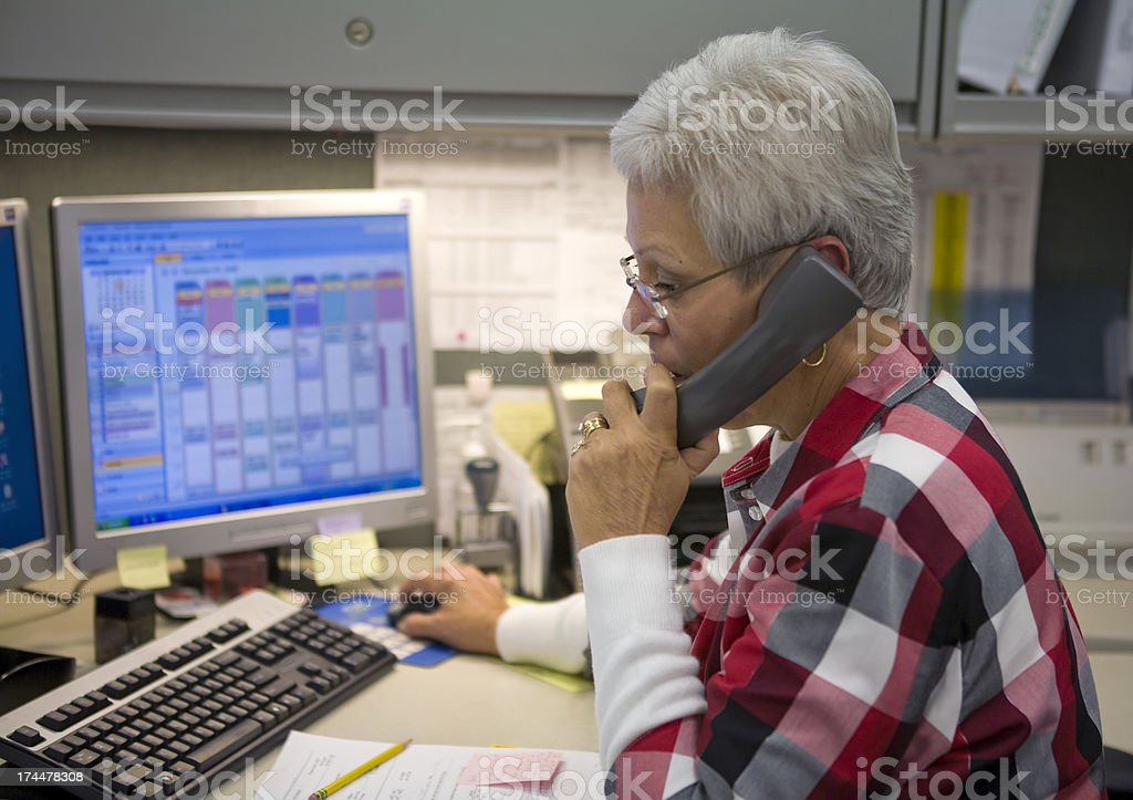 Administrative Specialist on Phone in Front of Computer stock photo