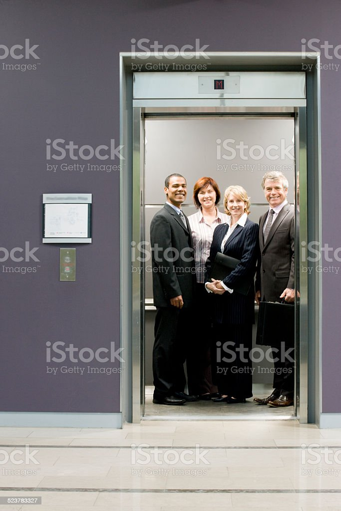 Administrative workers smiling in elevator stock photo