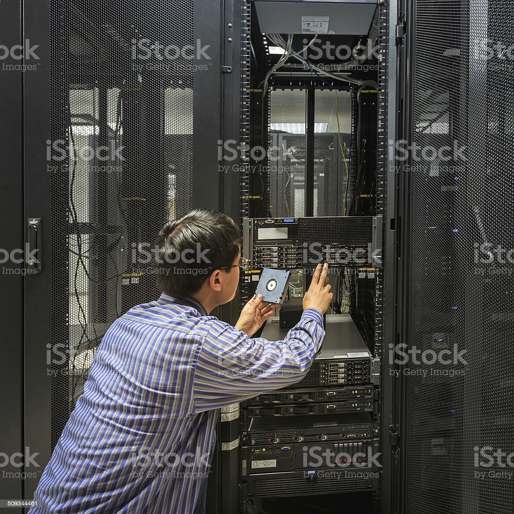 Administrator working on a server room stock photo