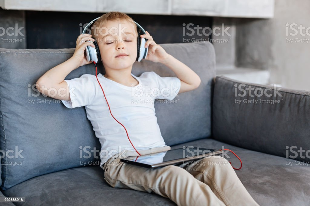 Admirable engaged kid relaxing on a sofa stock photo