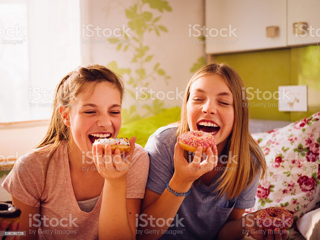 Adolescent girls eating coulourful doughnuts in a bright bedroom stock photo