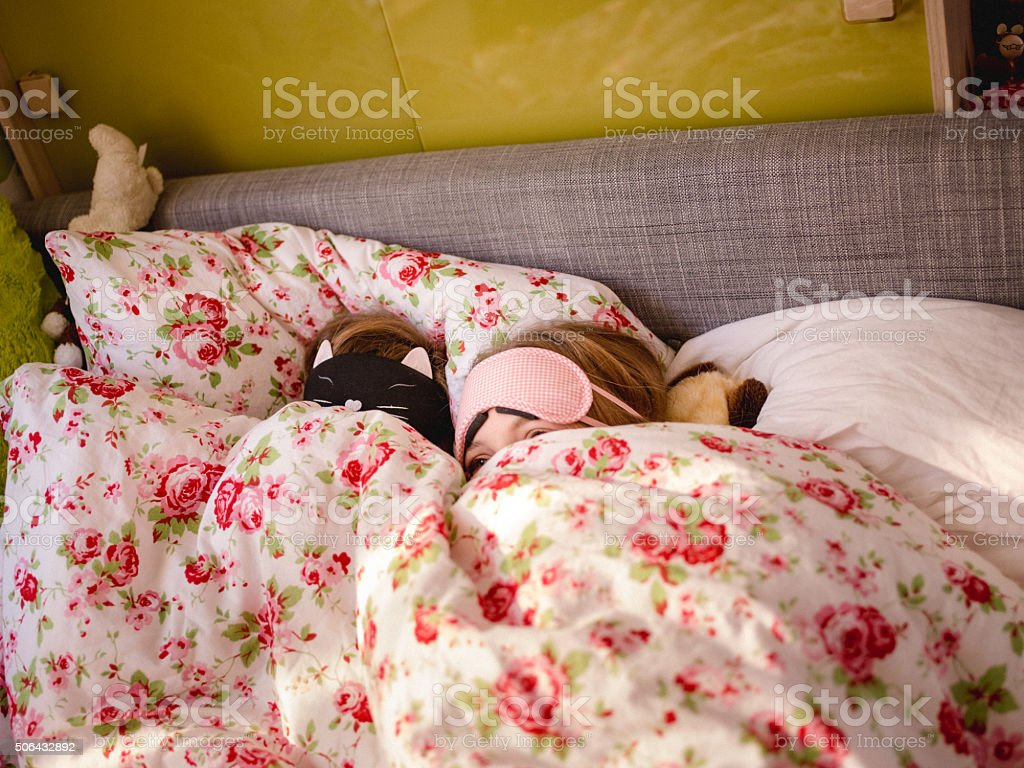 Adolescent girls hiding under the bed covers with sleeping masks stock photo