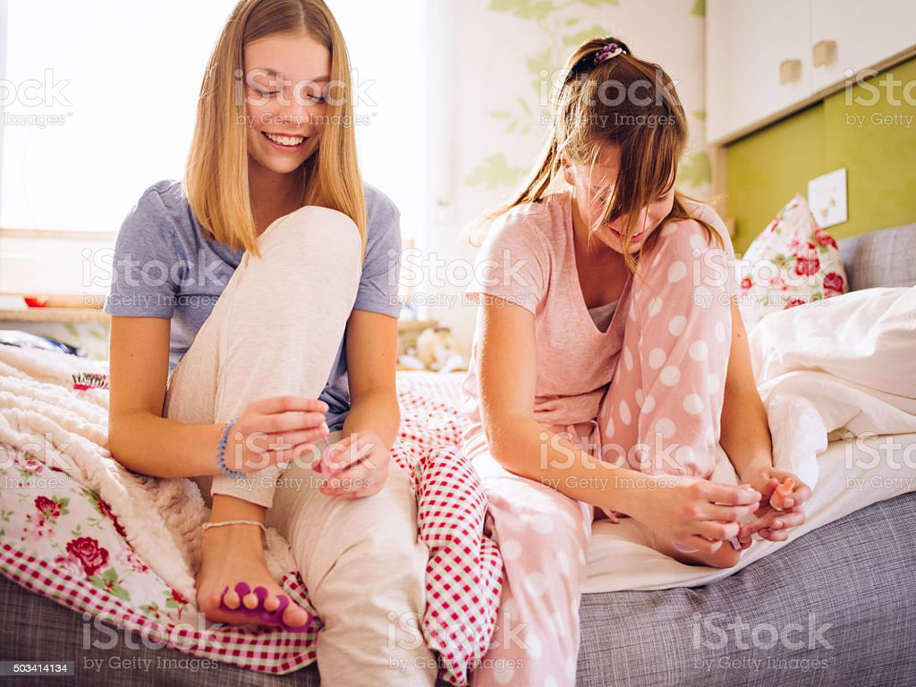 Adolescent girls in pyjamas on bed painting their toenails together stock photo