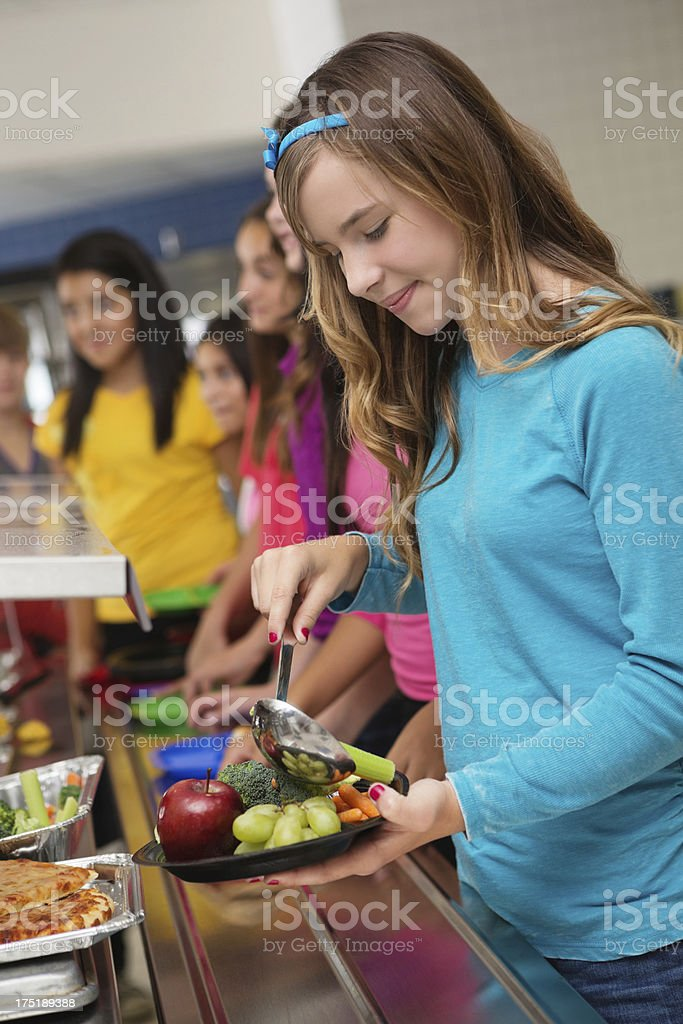 Adolescent student making healthy food choices in cafeteria lunch line royalty-free stock photo