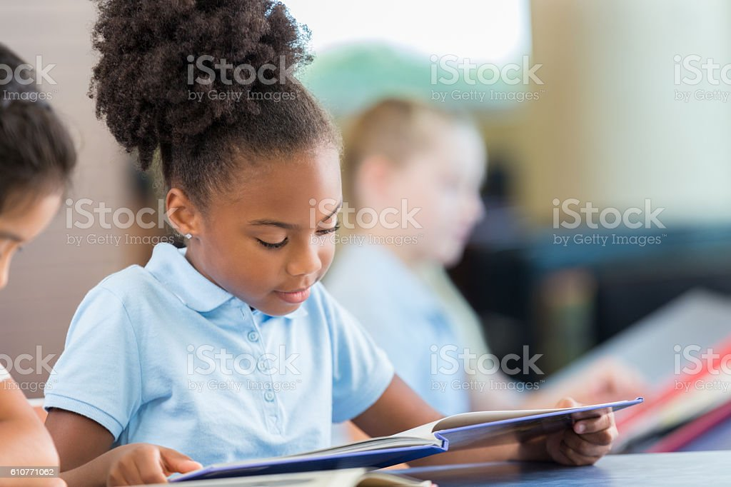 Adorable African American girl reading books in the school library stock photo