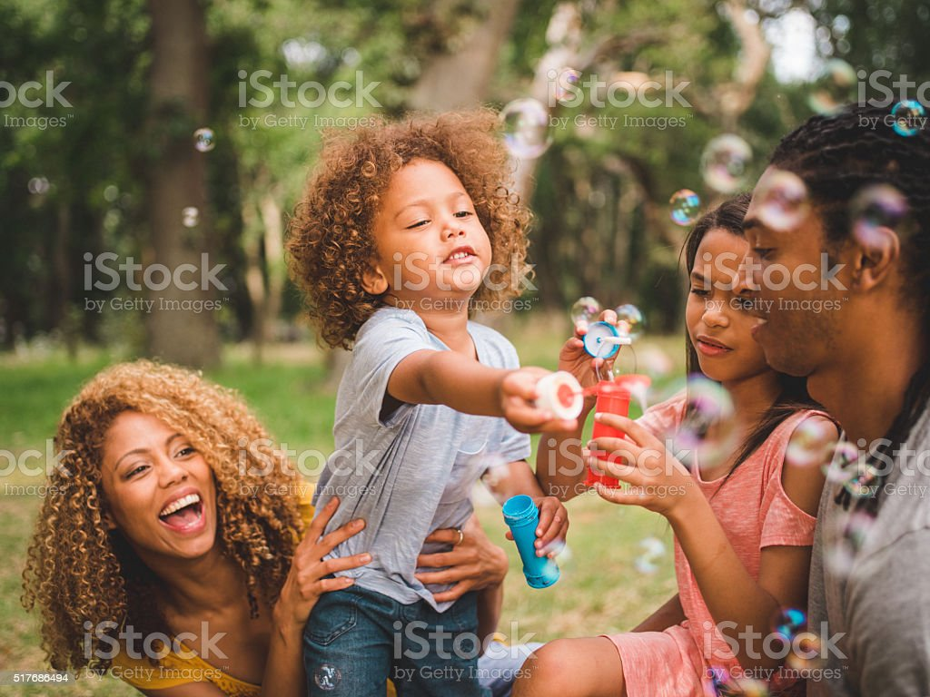 Adorable african-american curly haired toddler blows soap bulles stock photo