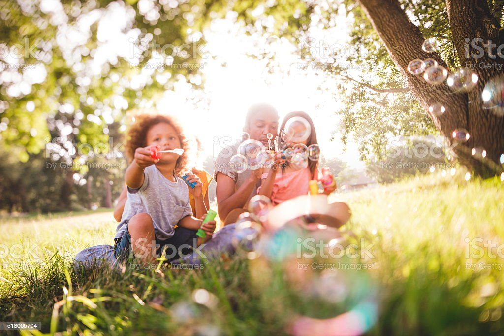 Adorable african-american family blows soap bubbles at eachother stock photo