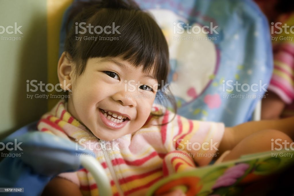 Adorable Asian Little Girl Reading in Playroom, Smiling, Copy Space royalty-free stock photo