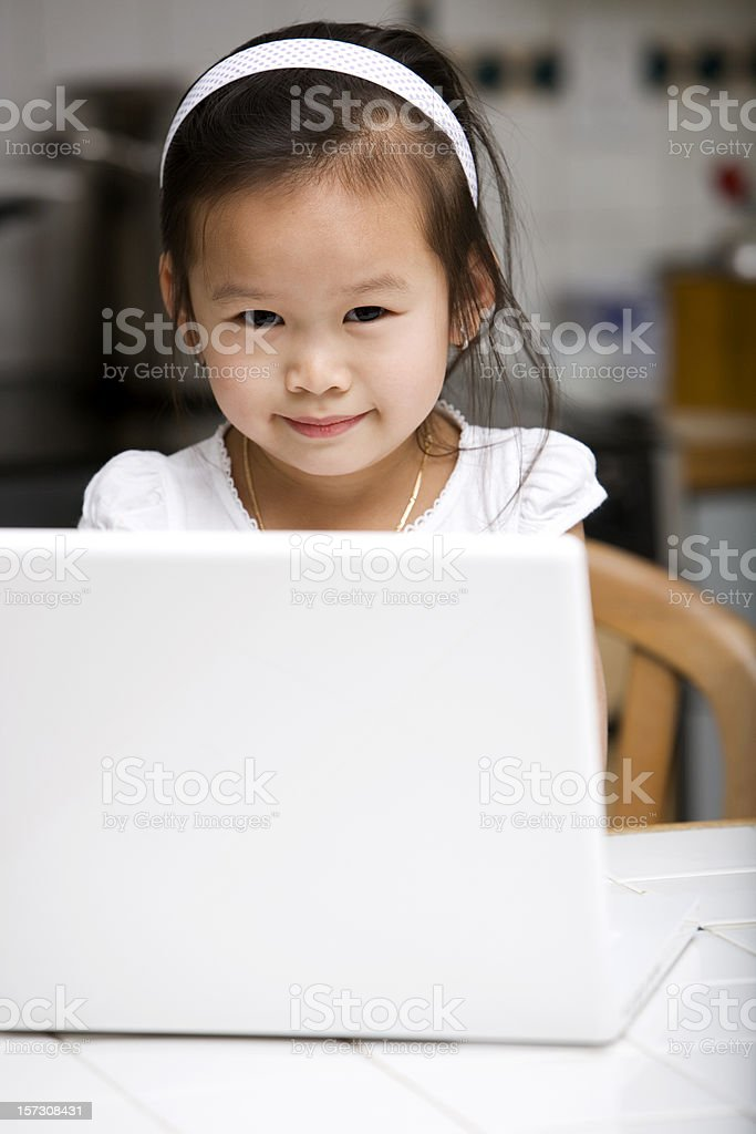 Adorable Asian Toddler Using Laptop at Home in Kitchen, Copyspace stock photo