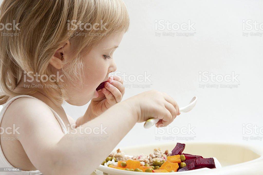 Adorable baby girl eating fresh vegetables stock photo