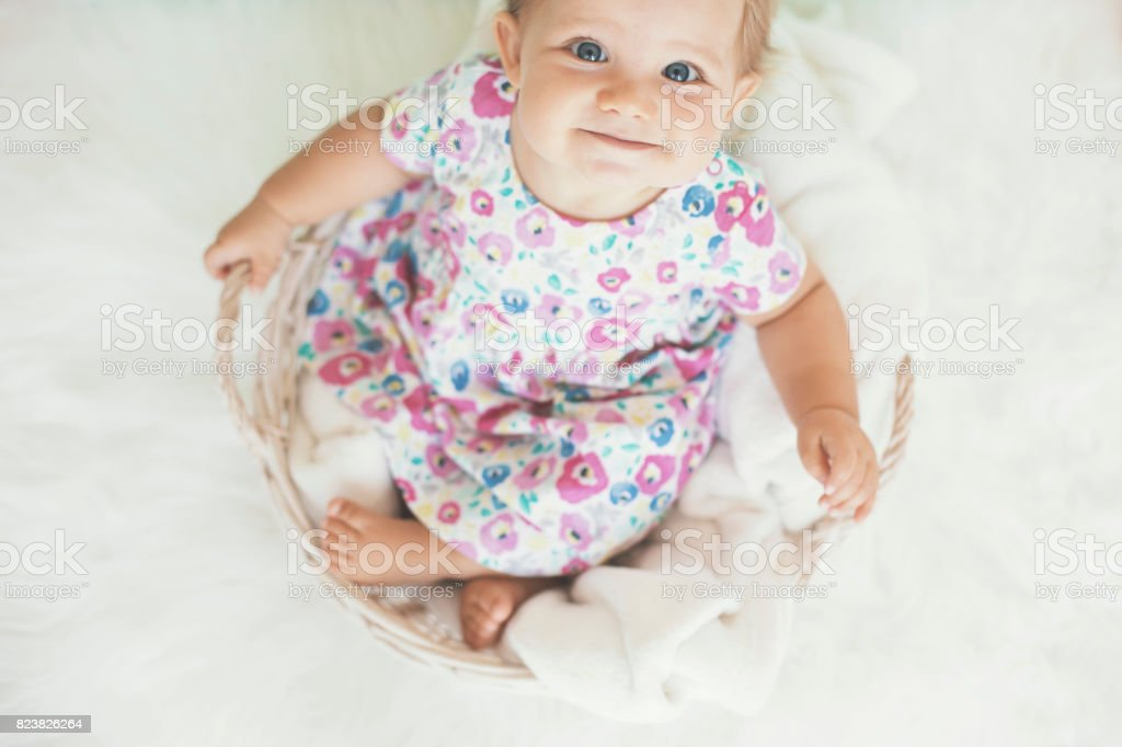 Adorable baby girl in basket with fluffy blanket stock photo