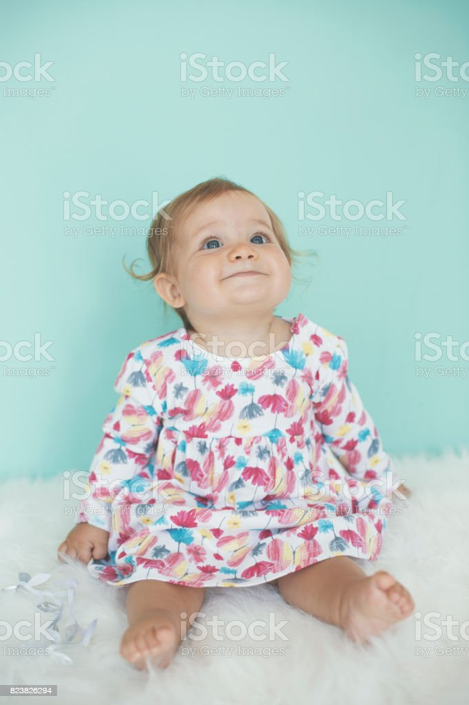 Adorable baby girl in floral dress stock photo