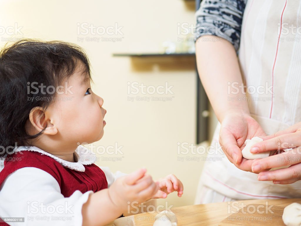 Adorable baby girl making gyoza with mom stock photo