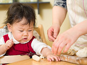 Adorable baby girl making gyoza with mom