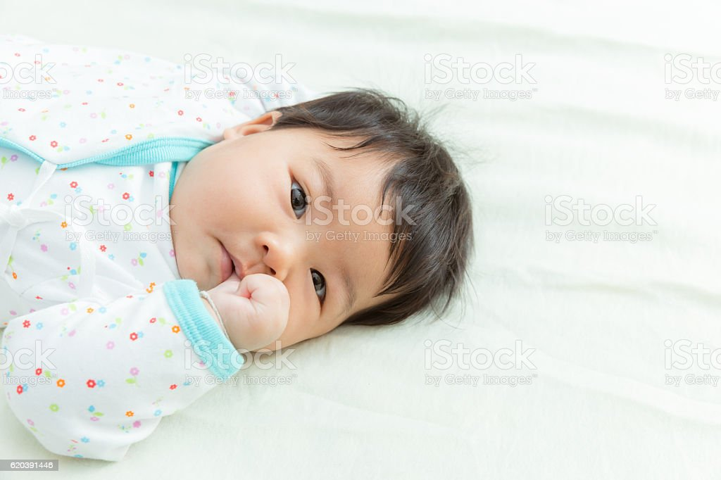 Adorable baby girl suck thumb on the bed. stock photo