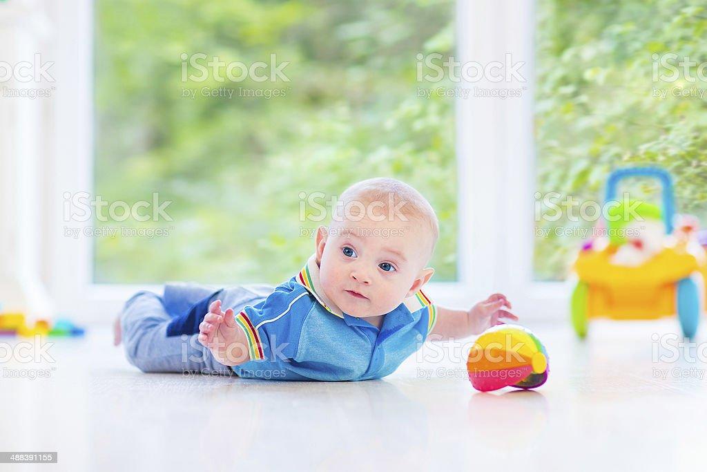 Adorable baby playing on floor next big garden view window stock photo