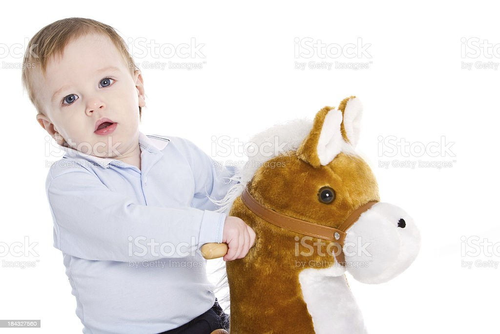 Adorable baby playing with hobbyhorse royalty-free stock photo