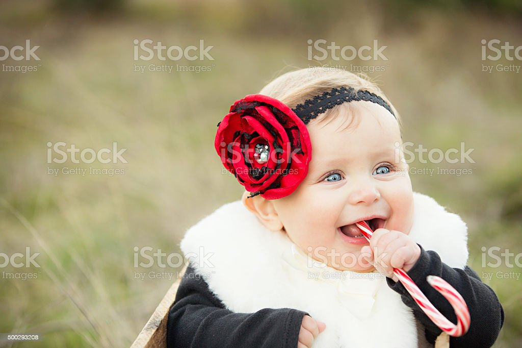 Adorable Baby with Candy Cane outdoors - Christmas Card stock photo