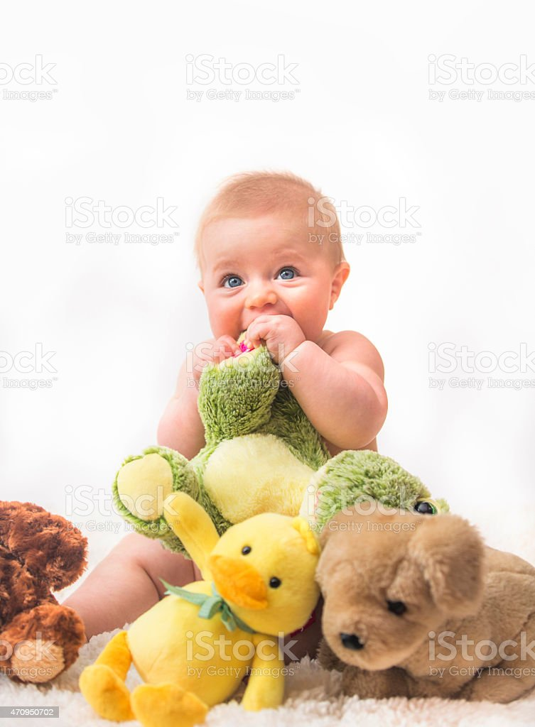 Adorable Blond Baby with Blue Eyes Playing With Toys stock photo