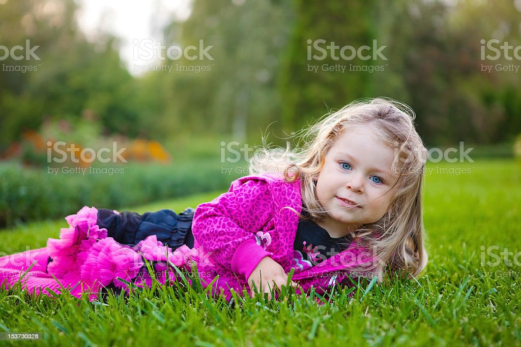 Adorable blonde little girl lying on green grass royalty-free stock photo