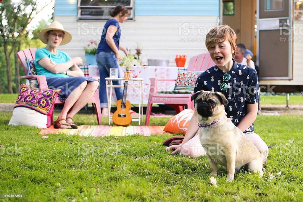 Adorable Boy and Pug Dog Vintage Camping with Friends Family stock photo