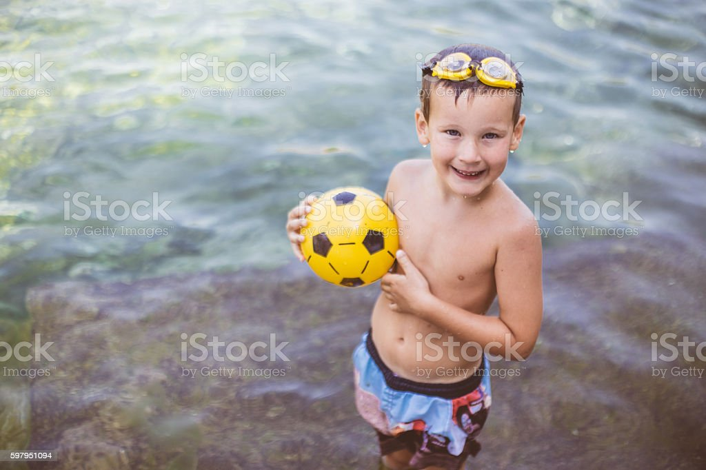 Adorable boy in goggles playing with football stock photo