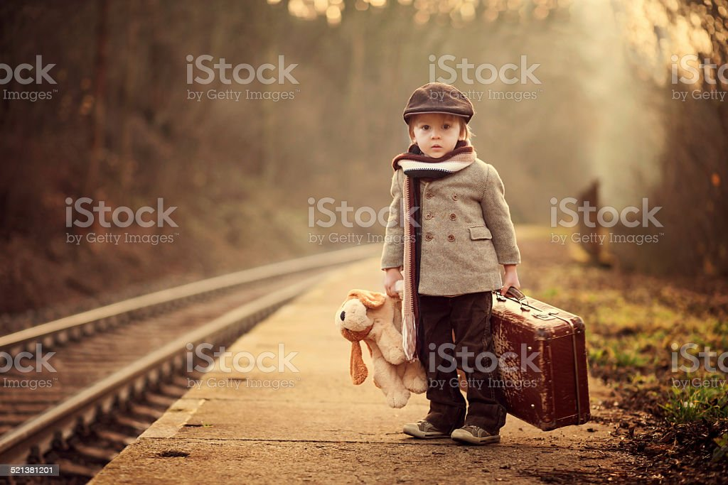 Adorable boy on a railway station, waiting for the train stock photo