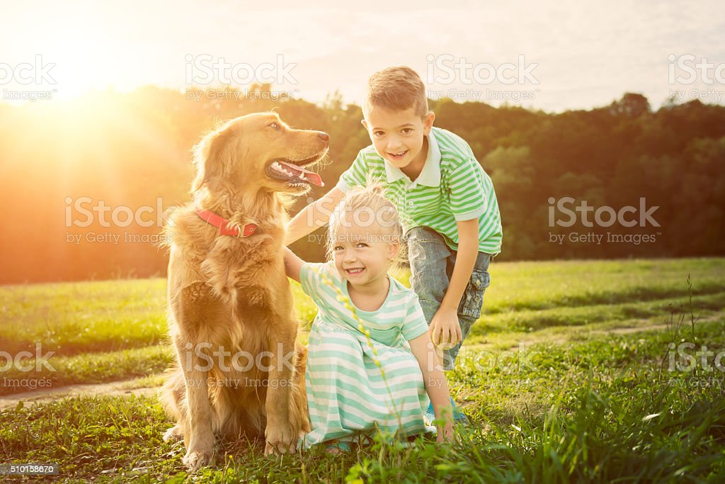 Adorable brother and sister playing with pet dog stock photo