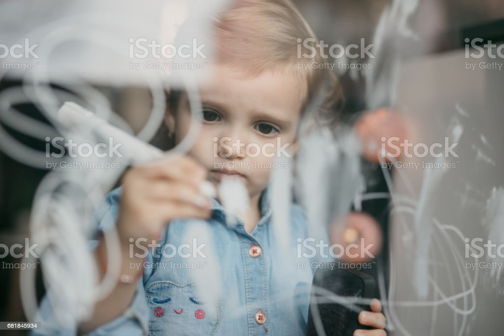 Adorable child draws objects on the window stock photo