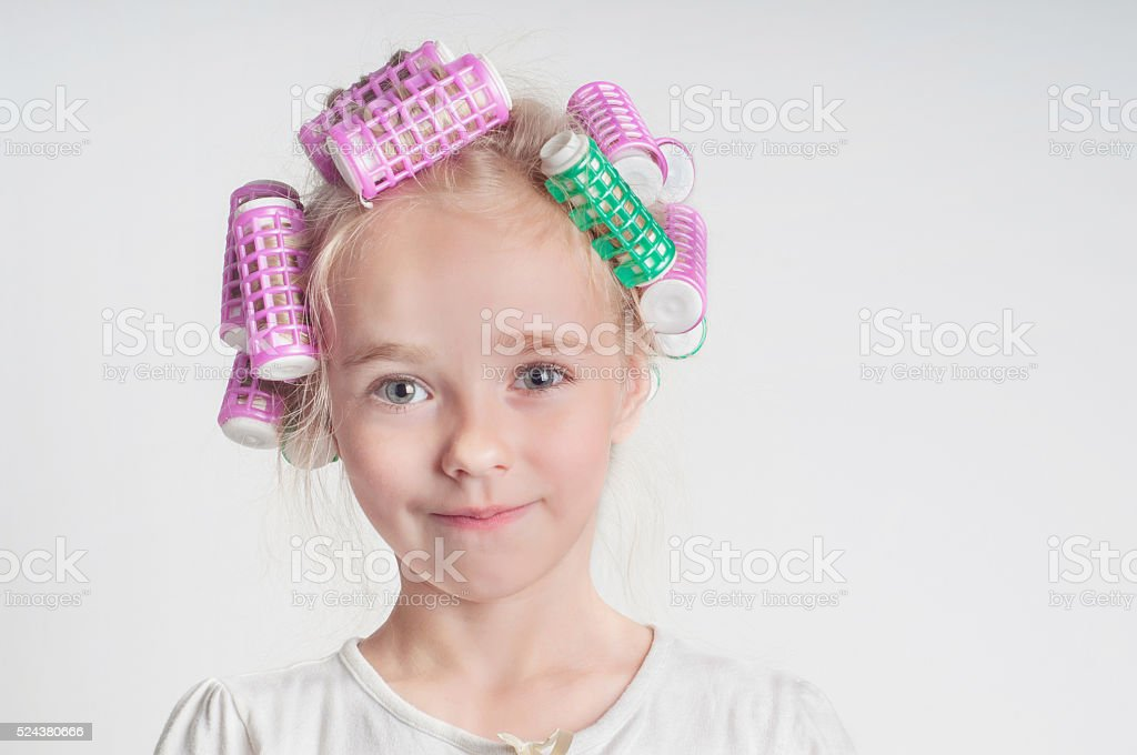 Adorable child girl portrait in curlers stock photo