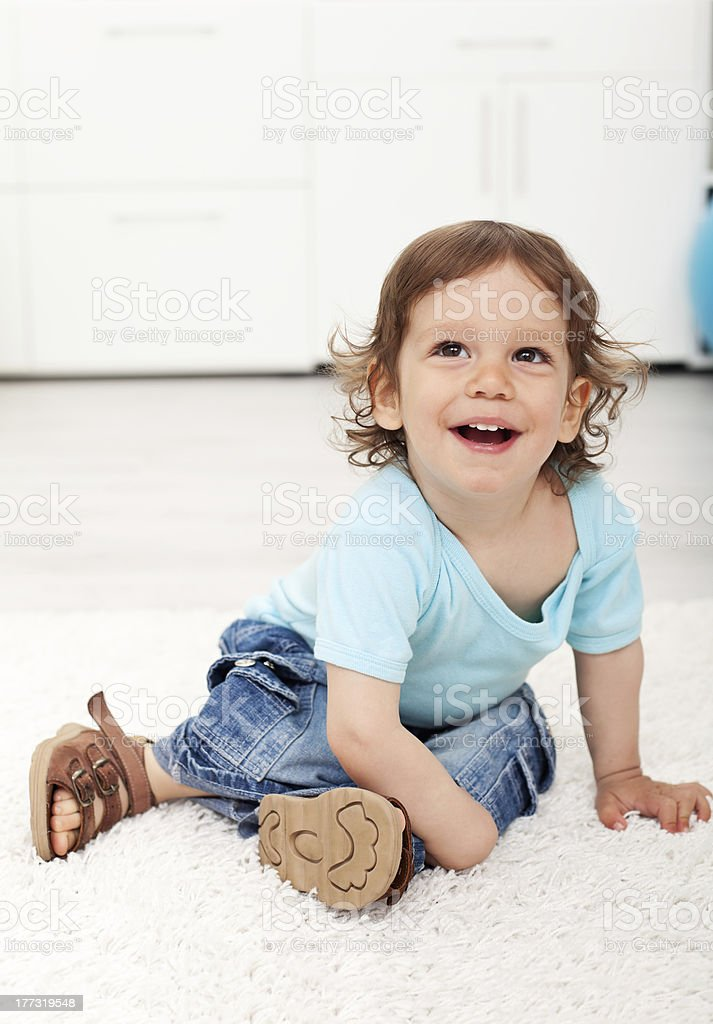 Adorable child laughing on the floor royalty-free stock photo
