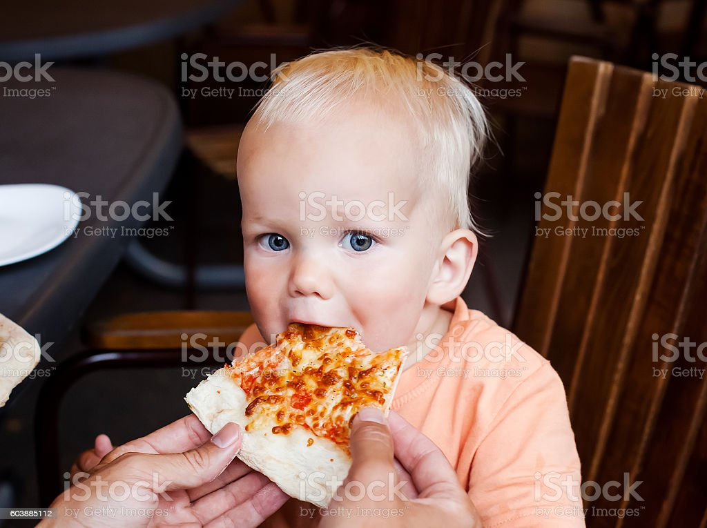 Adorable child toddler boy eating pizza slice at a restaurant stock photo